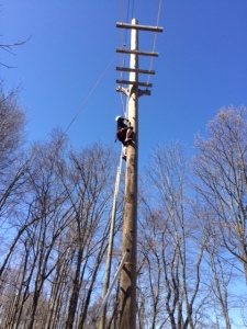 Climbing the pole to cross the high ropes.